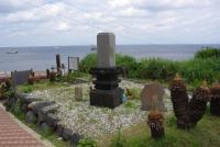 遥か海の彼方を見ている墓石